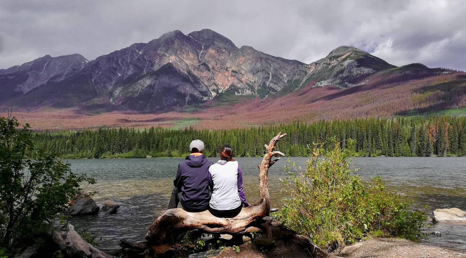 Dos personas contemplando el lago en las Rocosas de Canadá